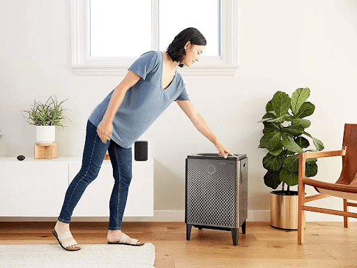 woman turning on air purifier in a room
